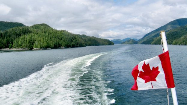 View of a Canadian lake taken from a speedboat with its wake trailing behind.