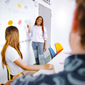 A female student showing and explaining something on a whiteboard in front of a class.